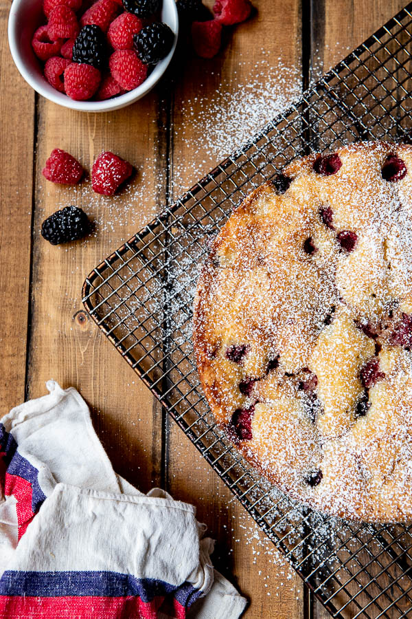 Butter cake with raspberry infused berries on a cooling rack with dusting of powdered sugar.