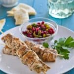 Cinnamon and cumin flavor these easy Baharat chicken skewers. With apomegranate relish, tahini yogurt sauce and pita make an exotic weeknight dinner.