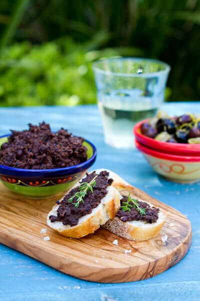 Olive tapenade in a bowl and spread on baguette slices