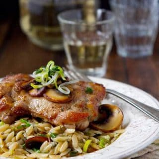 mushroom orzo risotto on a plate with a sauteed chicken thigh on top.