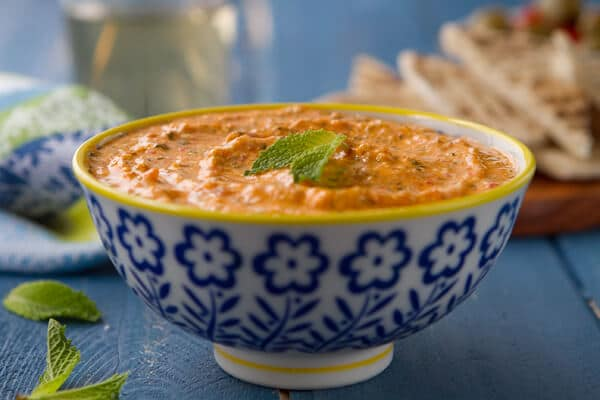bowl of kopanisti - a roasted red pepper dip recipe with pita.