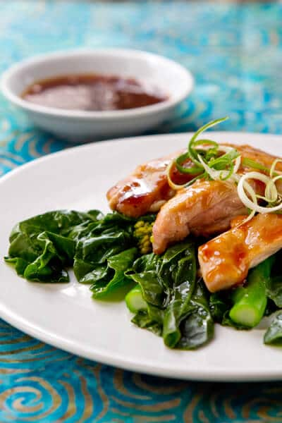 Gai lan with Tangerine glazed chicken on a white plate.