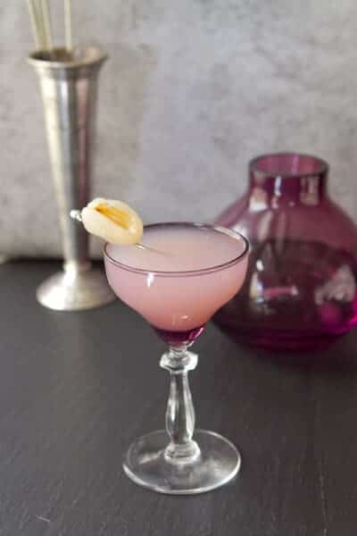Lychee cosmopolitan in a glass with lychee garnish.
