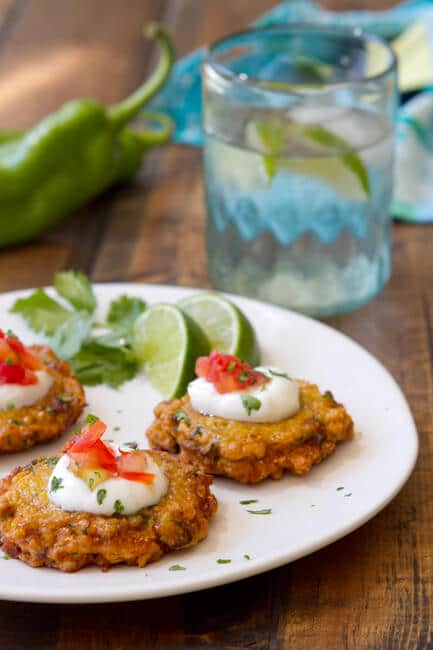 corn fritters on a plate garnished with sour cream and salsa
