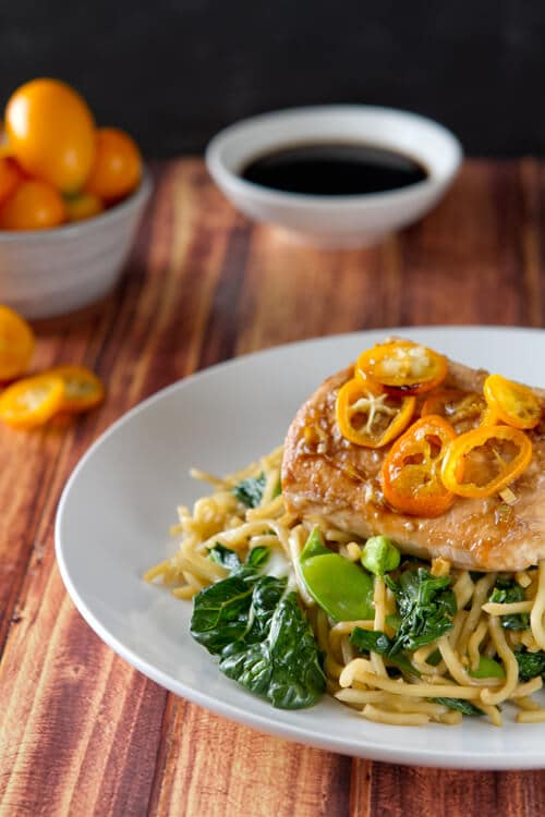 Salmon Yakisoba with Kumquats on a plate.