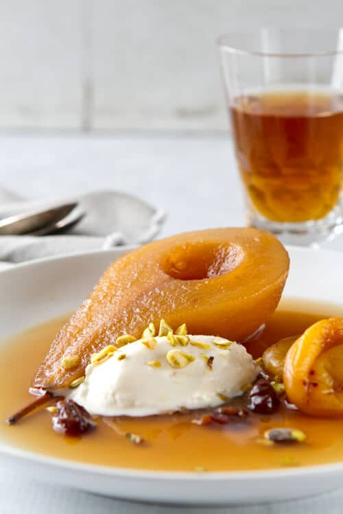 Tea poached pears with apricots and cherries on a plate.