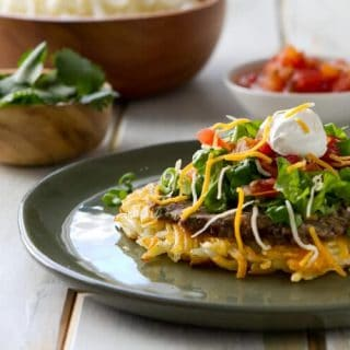 Frozen hash browns replace a tortilla in these Vegetarian Hash Brown Tostadas. Topped with lime and cilantro black beans it makes an easy 30 minute vegetarian dinner.