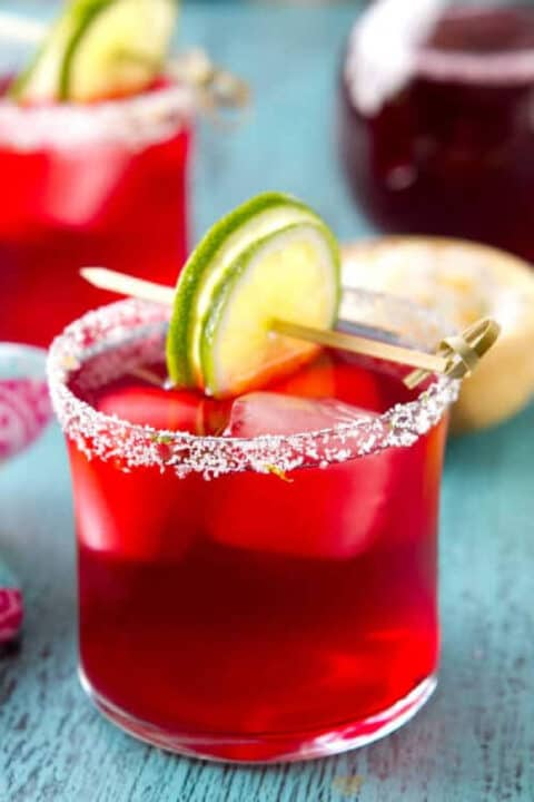 Hibiscus margarita in a glass with a lime garnish.