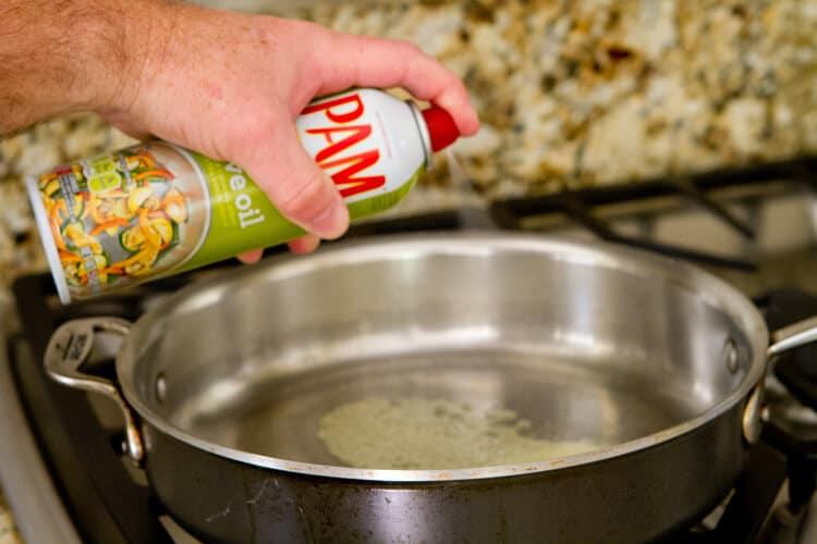 spraying pam on pan