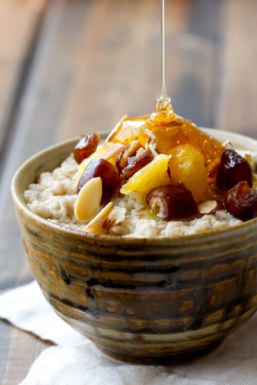 honey drizzled on a bowl of Orange and date Oatmeal- a healthy oatmeal breakfast