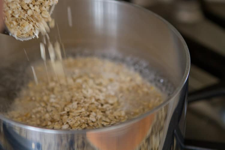 pouring oats into the pan for Orange and date oatmeal