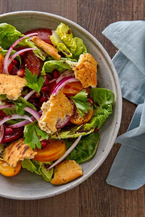 This Pomegranate Fattoush Salad riffs on the classic with pomegranate seeds and sumac with a sweet and tart flavor.