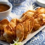 Crab rangoon on a platter with sweet and sour dipping sauce.