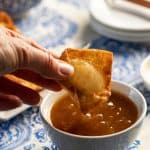 dipping a crab rangoon into the sweet and sour dipping sauce.