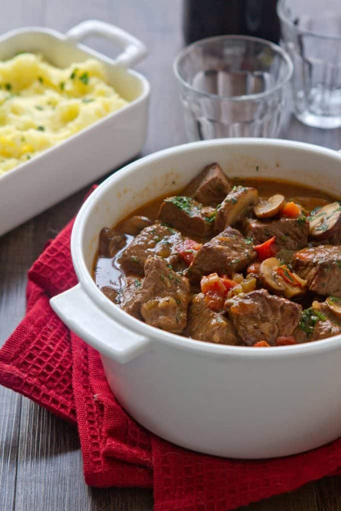 Casserole dish with Hunter's Stew and a side of potatoes