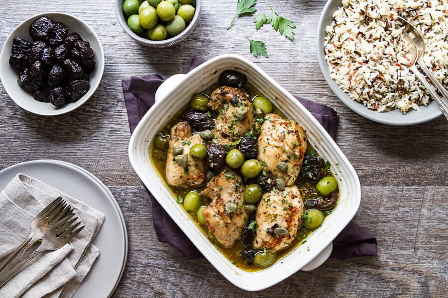 Overhead photo of Chicken marbella recipe with a bowl of wild and white rice.
