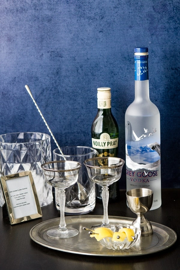 A bar set up for making vodka martini's - vodka, vermouth, glasses, a mixing glass and spoon, jigger, ice bucket and cocktail garnish on a platter.