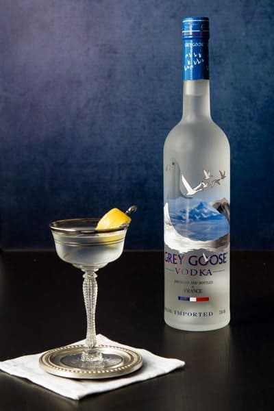 Bottle of Grey Goose Vodka and a glass with a grey goose vodka martini with a twist
