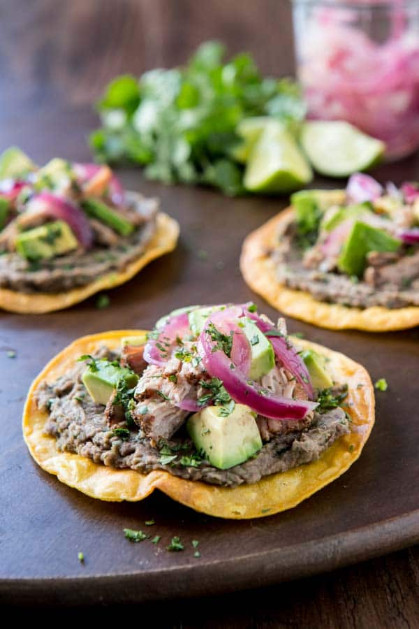close up of Tex mex slow cooker tostadas with a jar of pickled onions.