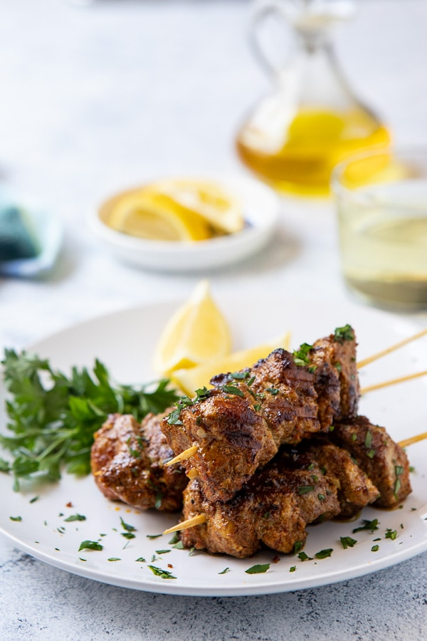 Plate with Ras El Hanout grilled Pork skewes with lemon and parsley