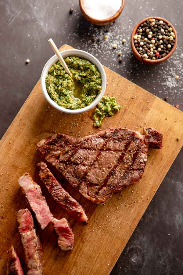 grilled ribeye steaks on a cutting board with Italian salsa verde.