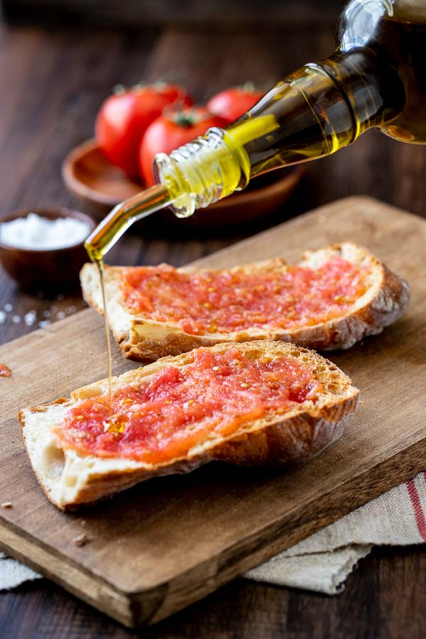 pouring olive oil on the Pan Con tomate.