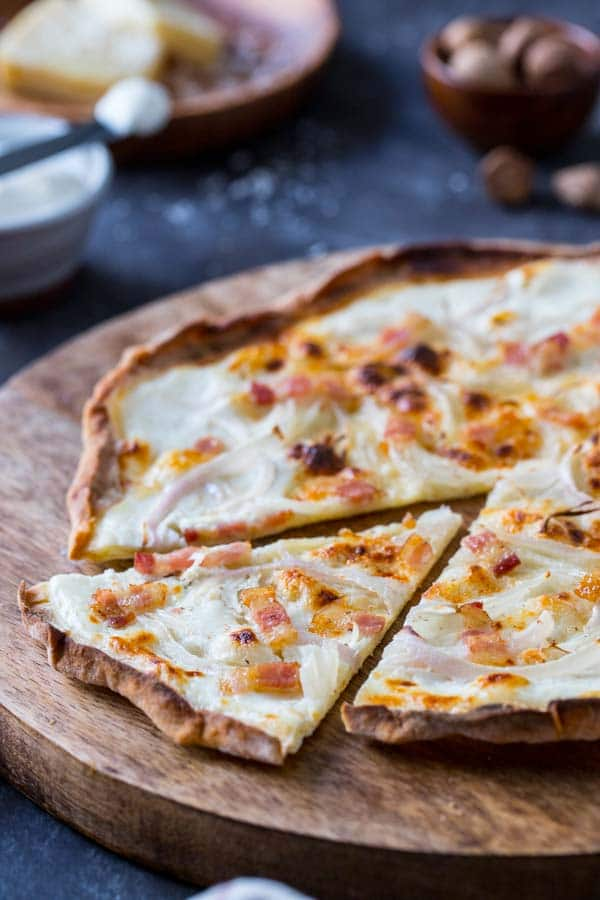 Tarte Flambee, or french pizza on a board with creme fraiche and cheese.