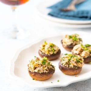 Platter of stuffed mushrooms with a glass of wine and plates in the background