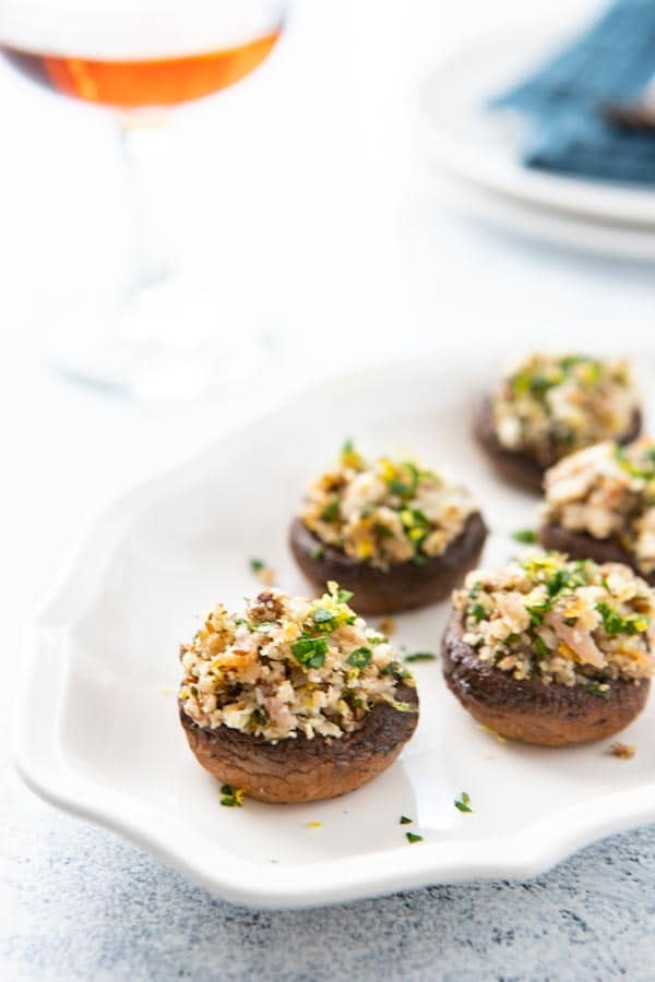 Stuffed Spanish  mushrooms on a platter with a glass of wine.