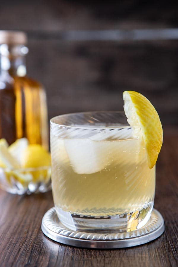 Old fashioned glass with a vanilla whiskey mule garnished with a lemon wedge.