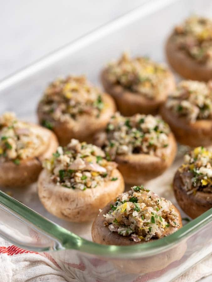 stuffed mushrooms in a casserole dish waiting to be baked.