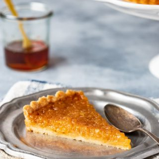 A single slice of treacle tart on a plate with golden syrup in the background.
