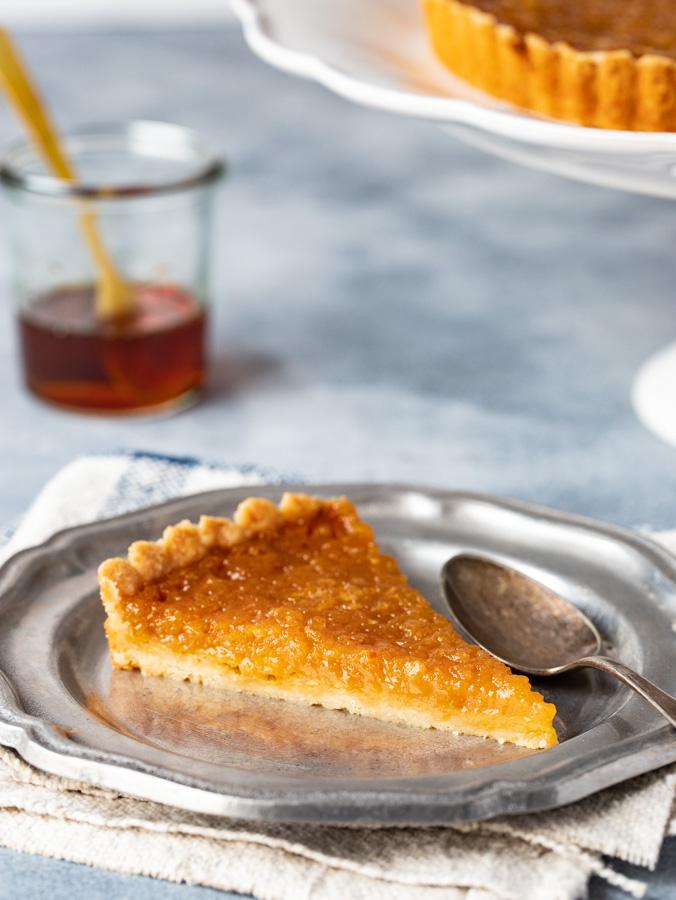 Slice of treacle tart on a plate.