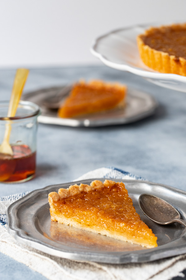 two slices of treacle tart on plates with jar of golden syrup