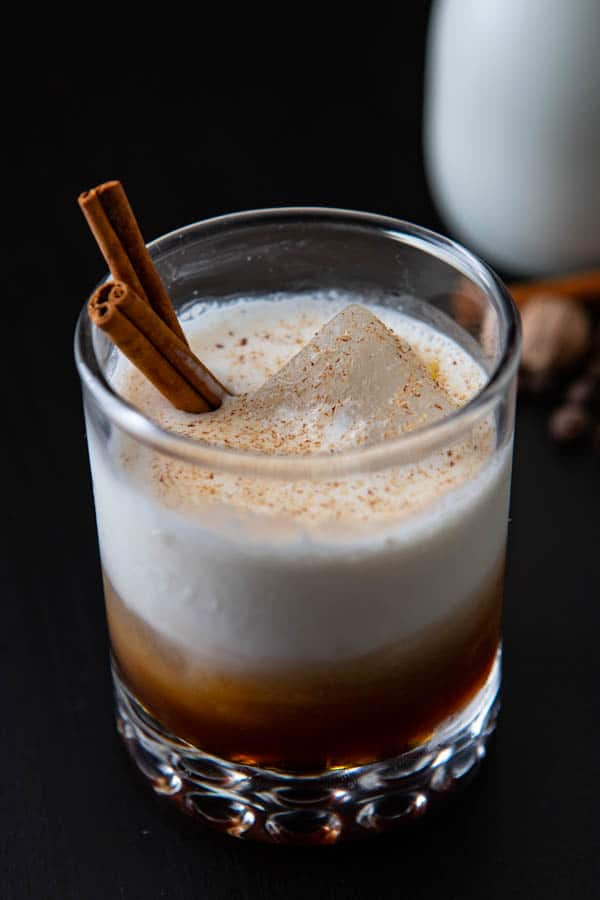 Glass with Kahlua and cream and cinnamon stirrers.