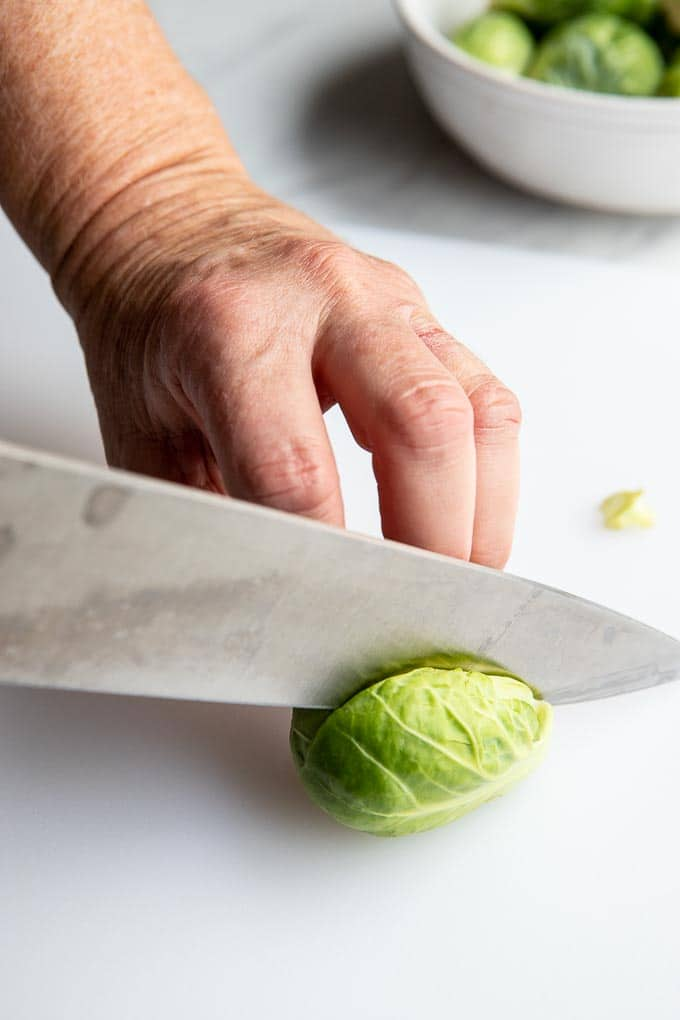Cutting a brussels sprouts in half on a cutting board