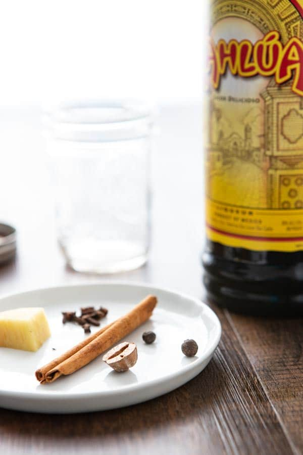 Ingredients for spice infused Kahlua  and cream recipe on a plate with a bottle of Kahlua.
