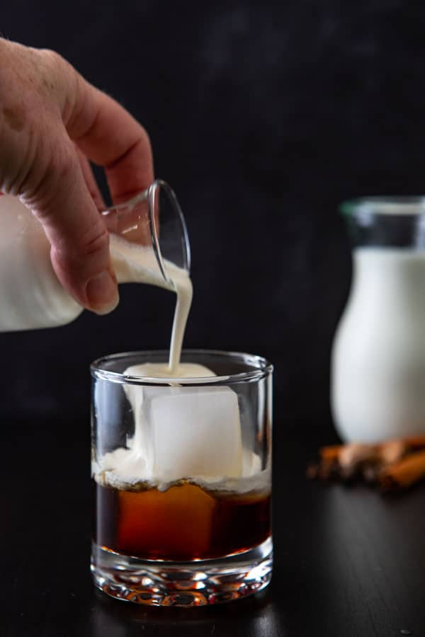 Pouring the cream over ice for the white russian drink.