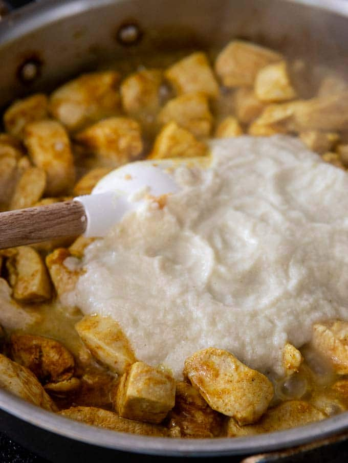 Step #3 for making chicken korma recipe: stirring the puree into the chicken in a saute pan