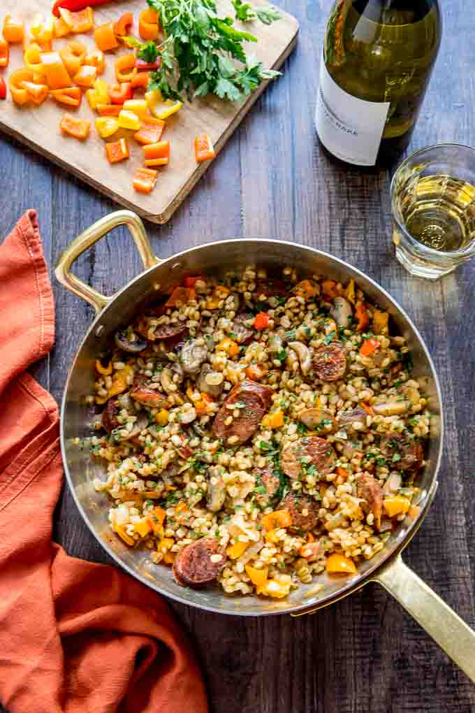 Overhead image of barley risotto with italian sausage and peppers with a glass of wine.
