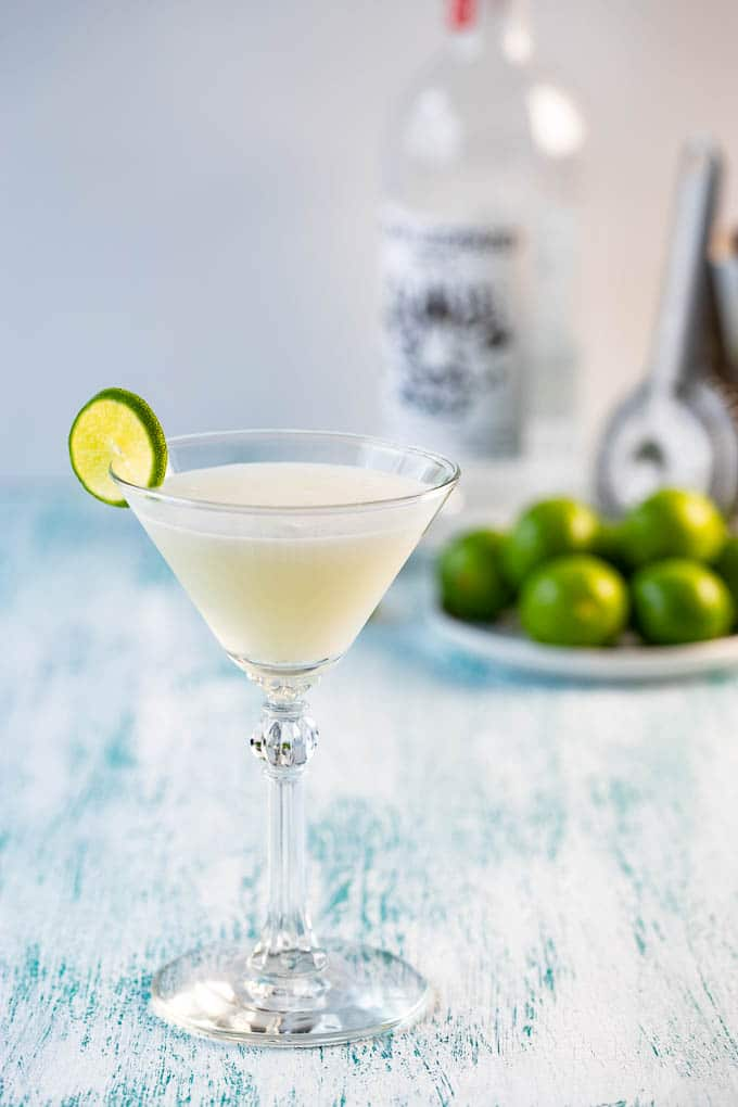 A key lime martini in a martini glass with a bottle of vodka and a dish of limes in the background.