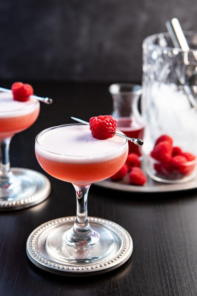 A coupe glass with the Clover Club Cocktail garnished with a single raspberry.