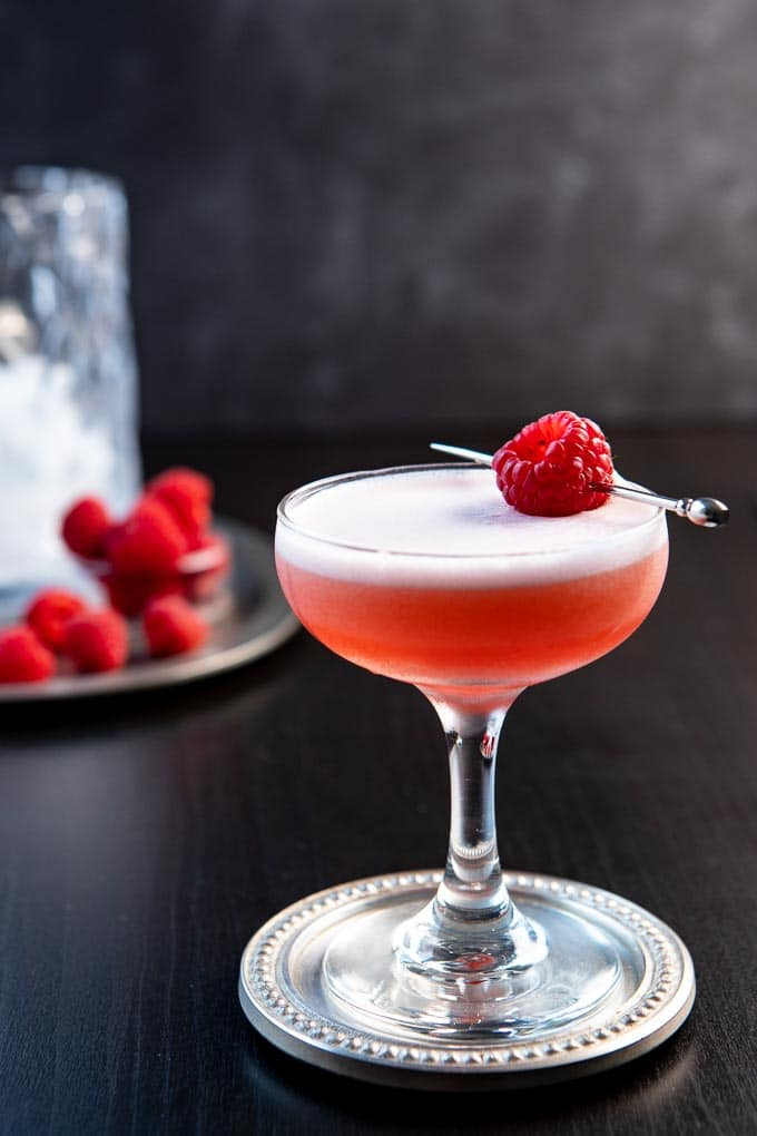 A glass of the clover club cocktail with a raspberry garnish.
