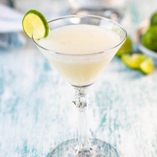A single glass of a key lime martini with a bottle of vodka and limes in the background.