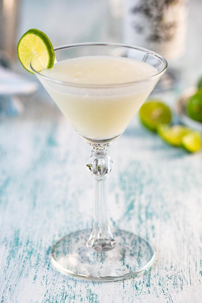 Martini glass with key lime martini garnished with a lime slice.