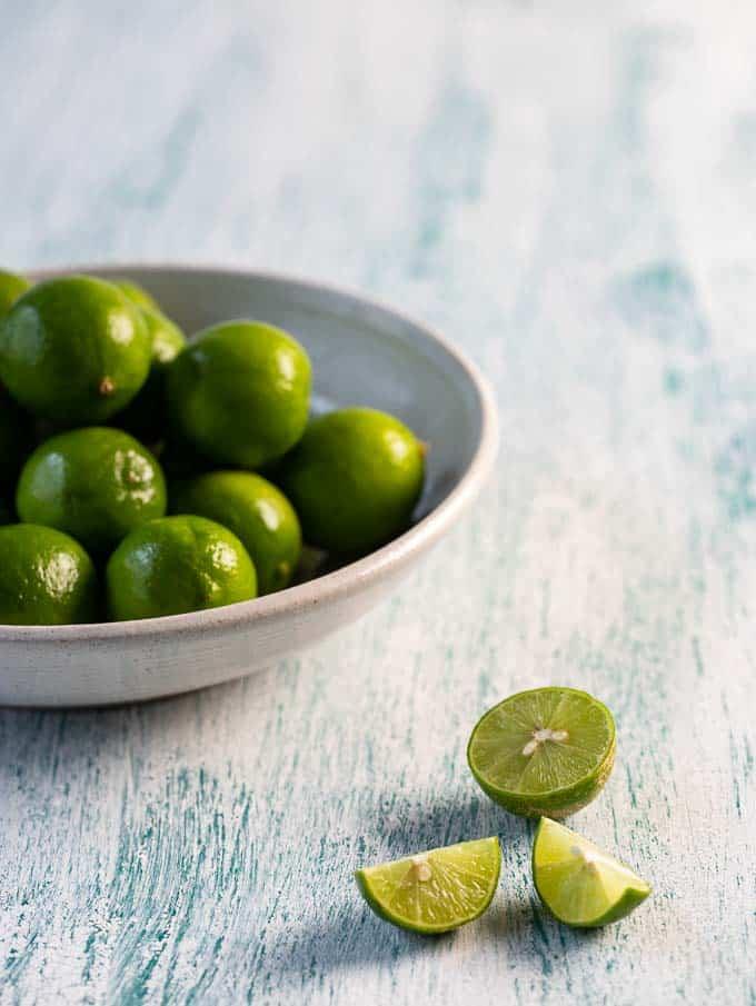 Bowl with key limes with a sliced key lime beside it to make key lime juice.
