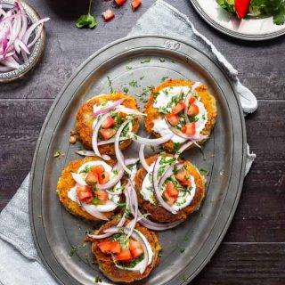Aloo tikki's on a metal platter and garnished with tomatoes, onions, yogurt, mint chutney and cilantro.
