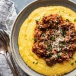 Shredded pork ragu on instant pot polenta in a bowl with a napkin and silverware