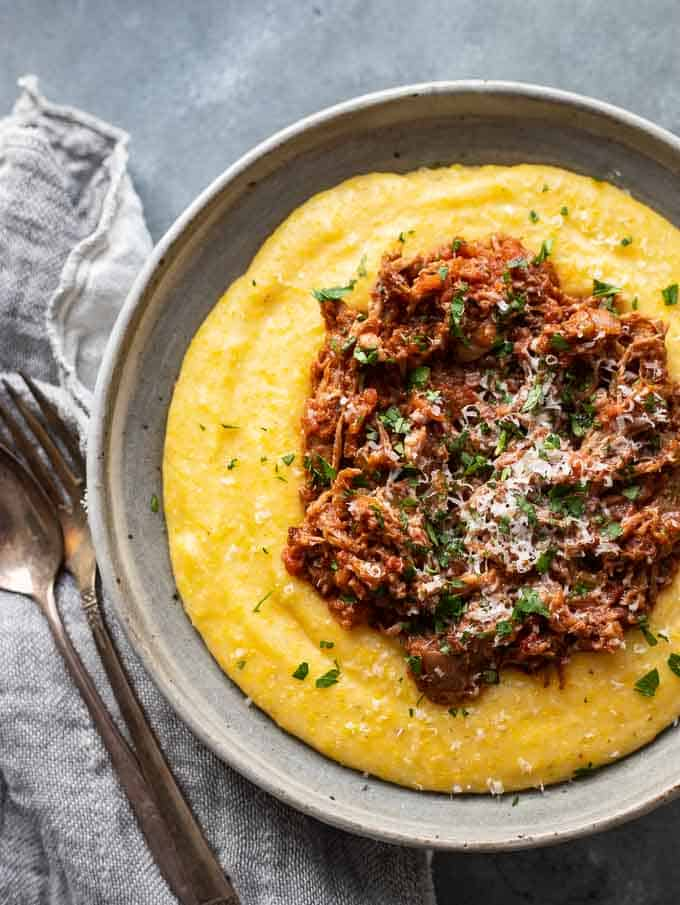 Overhead photo of an easy pork ragu recipe on top of polenta in a bowl with silverware and a napkin.