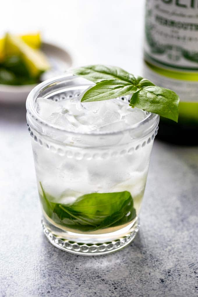Vermouth cocktail in a glass  with a basil leaf garnish.